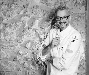 Portrait Jockl Kaiser vor Restaurantwand schwarz-weiß